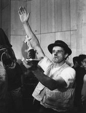 Black-and-white photograph of Joseph Beuys, blood dripping from his nose, right arm raised, left hand holding up a small sculptural object featuring a crucifix