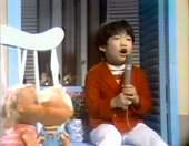 Video still showing a young boy wearing a red cardigan, singing into a microphone, with two dolls in the foreground