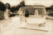 Black-and-white photograph of a car bonnet upon which sit a rectangular cake iced with the words 'lemon cake', with sections eaten from two corners, and three bottles of chocolate milk and a metronome. Two women stand next to the car.