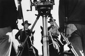 Fig.4 Black-and-white photograph with camera tripod in foreground, showing actors John Wayne and Dean Martin on horseback on a film set