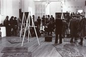 Black-and-white photograph of a studio with easels and blackboard panels. Joseph Beuys is at the centre while a crowd of people watch him