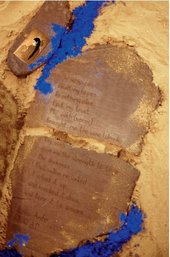 A stone tablet with writing carved into it, surrounded by patches of sand and dry pigment in yellow and blue.