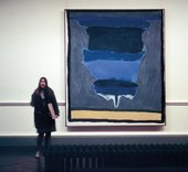 Photograph of Helen Frankenthaler's 1964 painting Cape, (Provincetown) hanging on a gallery wall with a woman standing next to it; the painting is abstract in a range of blues with a sandy yellow horizontal strip at the bottom