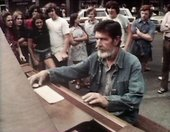 Video still showing John Cage sitting at a piano outdoors in Harvard Square, surrounded by people watching the performance