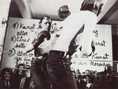 Black-and-white photograph of two men boxing in a ring in the foreground, with a crowd watching. Behind the audience is a large white panel with three statements written on it in German