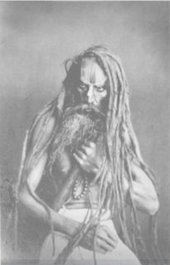 A portrait of a figure with long hair and a long beard, grasping a pole-like object and some beads against their chest.