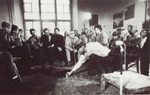 Black-and-white photograph in an art studio. Joseph Beuys sits on a chair and bends to draw in chalk on the floor. An audience sits around and watches.
