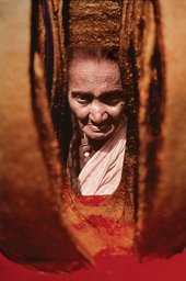 A close-up view of portrait photograph set within a sculpture made of vertical pieces of terracotta that frame it on either side.