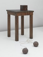 Installation featuring an accumulator – a kind of rechargeable battery in which energy can be stored – sits on top of a small wooden table and is attached by wires to two balls of clay on the floor