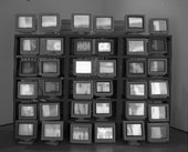 A display of thirty-six computer monitors presented in a grid-like structure.
