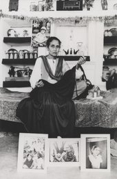 A figure sits on a bed holding a dark swathe of cloth, with three photographs displayed at their feet.