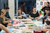 A group of people sit around a tablemaking objects using the craft materials that are in front of them.