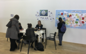 A small group of people sit writing and talking at a table, while another person looks at a large wall map withcolouredpieces of paper pinned to it.