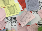 A close-up of a pinboard featuringcolouredpieces of paper with handwriting on them, and images of food and crockery.