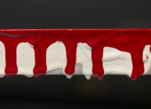 A horizontal view of part of the panel edge of Red Barn Door with five long red drip marks coming downwards, white drip marks seen underneath them, and shorter red drips seen over the top.
