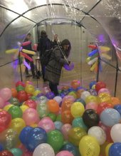 A view from inside a clear, tunnel-like structure, the lower half of which is filled with balloons, with a person standing at the entrance of the tunnel holding a balloon.