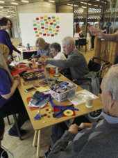 A group of older people sit working around a table that is covered with craft materials.