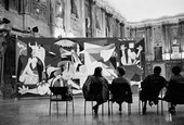 A black and white photograph of Picasso's painting Guernica installed within a large old Italian building, with four individuals sitting on chairs a short distance in front of the painting.