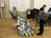 A person faces the camera and presents a large sculpture of a peacock with an arrayof brightlycolouredfeathers.