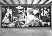 A black and white photograph of a room with a very large painting on the wall. The painting is semi-abstract and features a chaotic, overlapping composition of animals and human figures in distress in a domestic setting.