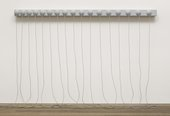 A grey sculpture consisting of a narrow, horizontal panel with seventeen hemispheres on its face, fixed to the wall around two metres above the floor, with long ropes from the centre of each hemisphere that hang down and rest in coils on the floor