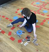 A person sits on the floor arranging pieces ofcolouredpaper and photographs.