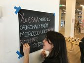 A person writes on a blackboard withcolouredchalk. The text reads 'Youssra, who is originally from Morocco, uses thyme rosemary…'