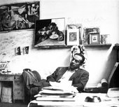 A black and white photograph of a man reclining in a chair, with books and papers in front of him and on the wall behind him a poster of Picasso's painting Guernica, a painting of a man eating spaghetti, and various black and white portrait photographs.
