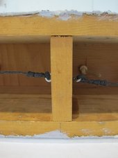 A close-up view showing two horizontal pieces of wood connected by a vertical one, with a vertical pencil line drawn above the central point of the vertical piece of wood.