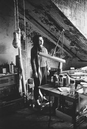 A black and white photograph of the artist in a bare-walled studio space, with rounded objects hanging from the ceiling on ropes to her right, and an array of long sculptural forms, bottles and glasses on a table in front of her.