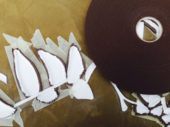 The brown surface of Double Exposure is seen from above, with a large roll of foam draught excluder on the left, surrounded by leaf and stalk shapes made of paint, draught excluder and masking tape.