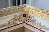 In the photograph the outside section of the frame is gilded on one edge, whereas most of the rest is still white, with areas and lines of dark red bole in preparation for gilding.