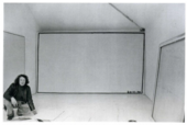 Bob law photographed crouching in a gallery space in front of a large canvas with a black rectangle drawn around the edge.