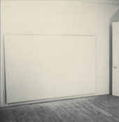 A photograph taken at an angle of a large white canvas hanging just off the floor in a room with a wooden floor.
