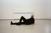 A photograph of Uglow reclining in a gallery, looking at a canvas with a single horizontal line across its middle.