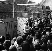Black-and-white photograph of Tom Hudson speaking in front of a painting in a room full of standing students.