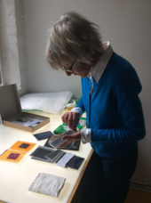 A person stands by a table, holding photographic negatives and perhaps in the process of explaining something. On the table are an array of photographic materials.