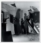 Black and white photograph of people installing an exhibition