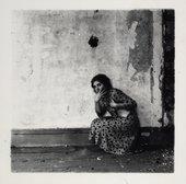 Francesca Woodman crouching by a wall