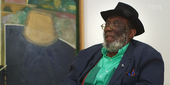 Portrait of Frank Bowling sitting in a chair in front of a painting
