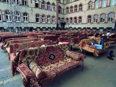 Series of sofas covered by patterned rugs and arranged in rows in a courtyard