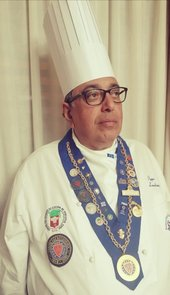portrait of a man with a tall chef hat, glasses, and a sash around his neck covered in cooking awards.