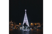 Two people ride on a bike in front of a lit christmas tree