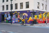 A person cycles past a mural covering two sides of a building