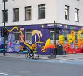 A person cycles past a mural painted on a building