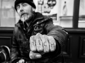 A man holding out a fist. The word rich is tattooed on his knuckles