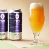 beer in a glass with two tins behind it that say 'tate and haze beer' on it