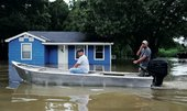 People drive through a flooded road by boat as they visit their neighbourhood on 16 August 2016 in Sorrento, Louisiana