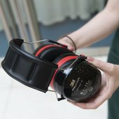 A person holds a set of ear defenders.
