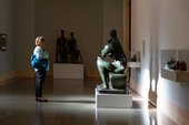 a woman stands in front of a Henry Moore sculpture